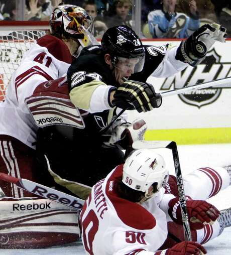The Penguins' Matt Cooke (24) gets tangled up with Coyotes goalie Mike Smith and Antoine Vermette. Smith made 26 saves in the Coyotes' loss. Photo: Gene J. Puskar / AP