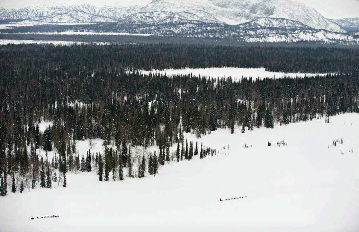 Two teams competing in the Iditarod Trail Sled Dog Race make their way between the Skwentna and Finger Lake checkpoints, heading toward the Alaska Mountain Range, on Monday, March 5, 2012.