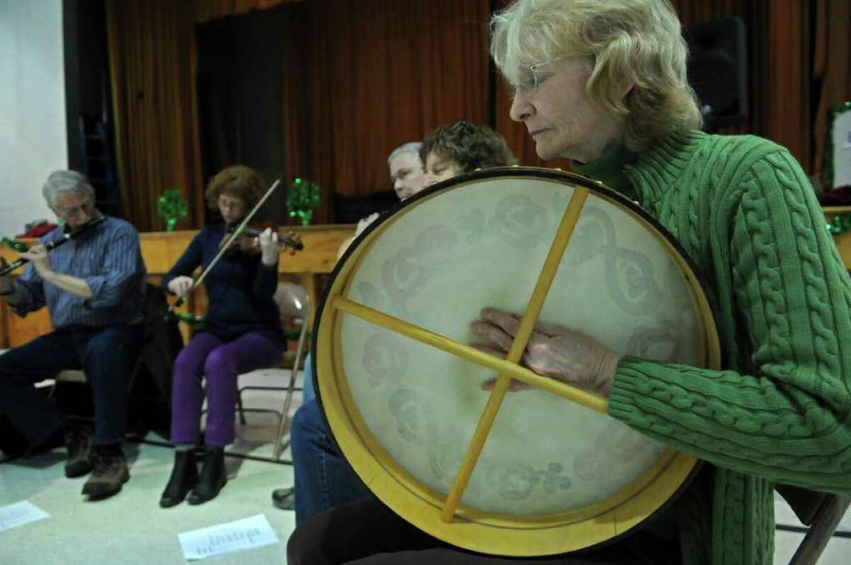 Cathy Clarke of Saratoga Springs plays the bodhran while performing with fellow members of Albany Comhaltas during the 8th annual Irish Fest, at St. Francis of Assisi Church on Sunday March 4, 2012 in Albany, N.Y. (Philip Kamrass / Times Union )