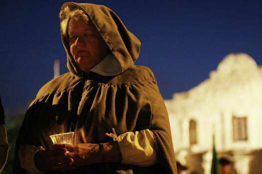 Cathy Jones, of the San Antonio Living History Association, holds one of 13 candles during the presentation of the 176th anniversary remembrance of the Battle of the Alamo at Alamo Plaza, Tuesday, March 6, 2012. Thirteen candles were lit in remembrance of the 13-day siege of the Alamo. Photo: Jerry Lara, San Antonio Express-News / © 2012 San Antonio Express-News
