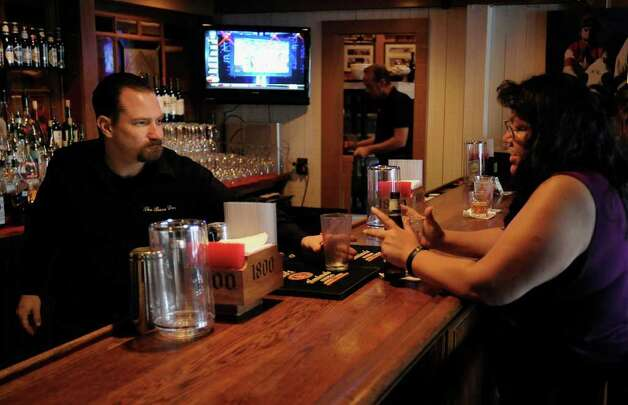 Bartender Brian Rager, left, serves Denise Saenz at the Barn Door Restaurant bar, Monday, March 5, 2012, in San Antonio. Photo: Darren Abate, Darren Abate/Special To The Express-News