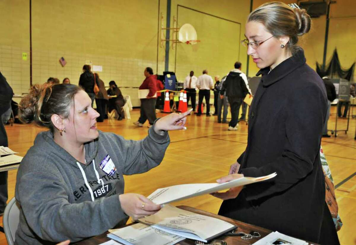 Election inspector Katherine Taylor, left, gives a ballot and some instructions to Brittney Belz before she votes at Schenectady High School Tuesday November 2, 2010. (John Carl D'Annibale / Times Union)