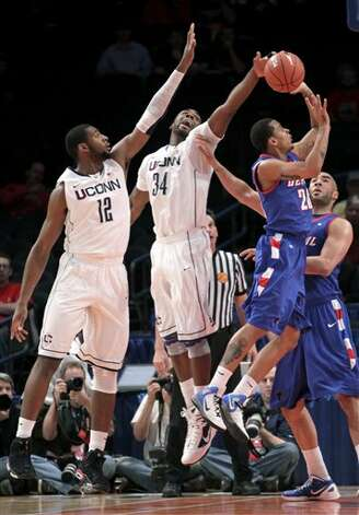 Connecticut's Alex Oriakhi, second from left, gets a hand on a shot by DePaul's Brandon Young, while Connecticut's Andre Drummond, left, and DePaul's Krys Faber look on during the first round of the Big East NCAA college  basketball conference tournament in New York, Tuesday, March 6, 2012.   (AP Photo/Seth Wenig) / AP2012