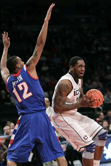 Connecticut's Alex Oriakhi, right, tries to get around DePaul's Cleveland Melvin (12) during the