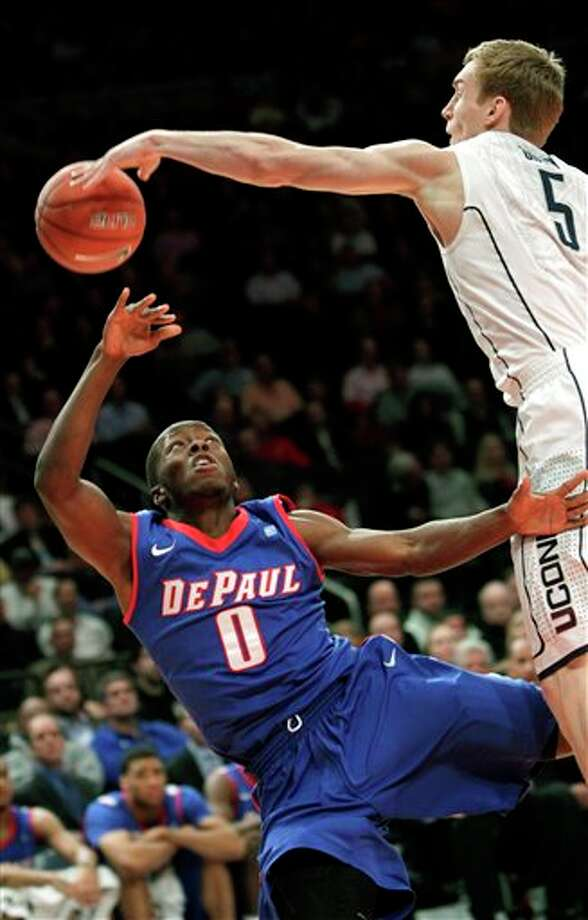 Connecticut's Niels Giffey, right, blocks a shot put up by DePaul's Worrel Clahar during the first round of the Big East NCAA college basketball conference tournament game, Tuesday, March 6, 2012, in New York. Connecticut beat DePaul 81-67. (AP Photo/Seth Wenig)