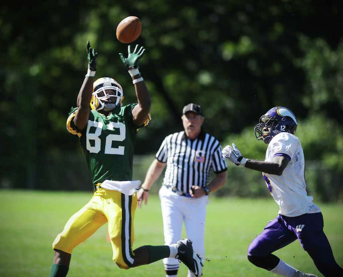 Trinity Catholic High School's Shawn Robinson reaches for the ball and runs it in for a touchdown against Westhill High School's Zack Emilcar in city rivalry football action at Trinity in Stamford, Conn. on Saturday October 2, 2010.