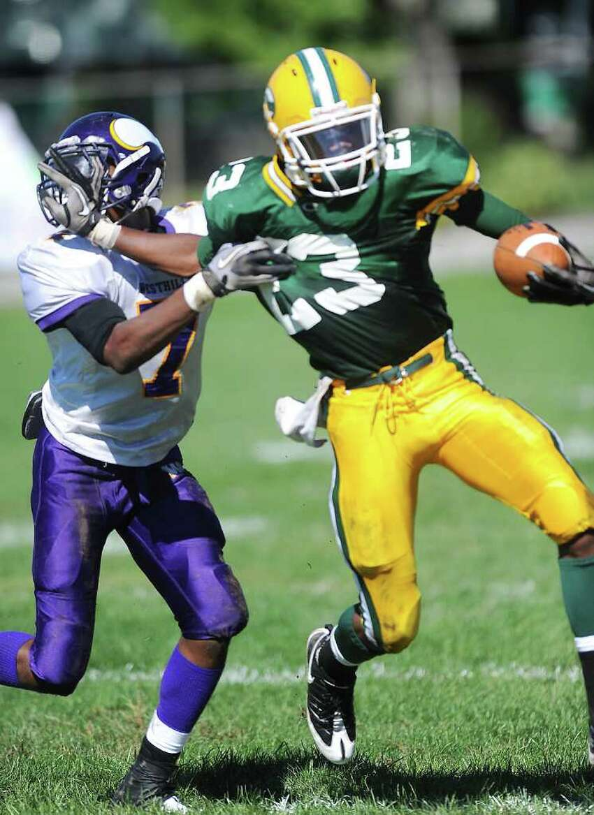 Trinity Catholic High School's Tre Crumbley carries the ball with pressure from Westhill High School's Kieran Bowman in city rivalry football action at Trinity in Stamford, Conn. on Saturday October 2, 2010.