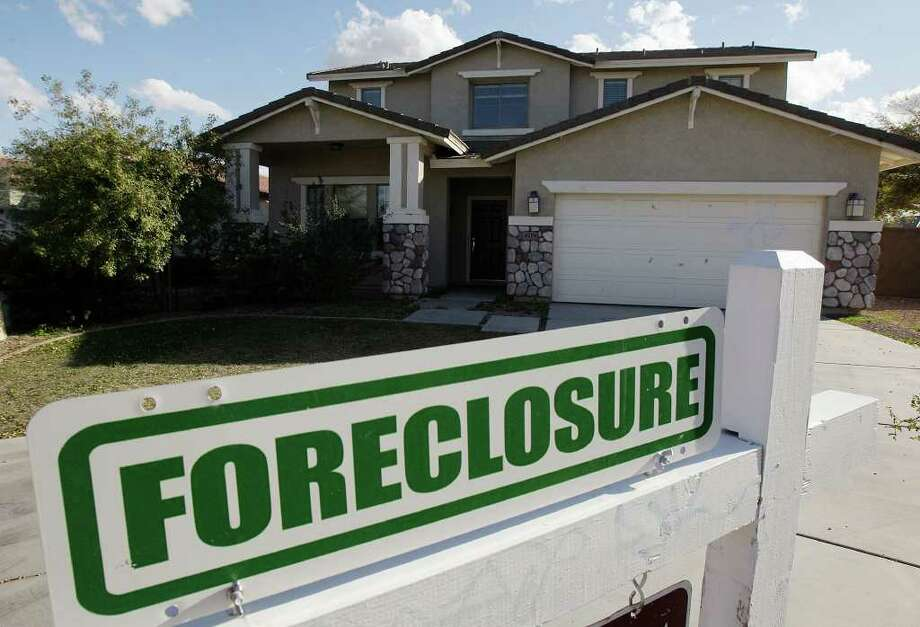 ** HOLD FOR RELEASE UNTIL 12:01 A.M. EDT THURSDAY, APRIL 16. THIS PHOTO MAY NOT BE PUBLISHED, BROADCAST OR POSTED ONLINE BEFORE 12:01 A.M. EDT THURSDAY  ** FILE - In this Feb. 17, 2009 file photo, a foreclosure sign sits outside a home for sale in Phoenix. RealtyTrac releases foreclosure data for the first three months of the year on Thursday, April 16, 2009. Photo: Ross D. Franklin, AP / AP