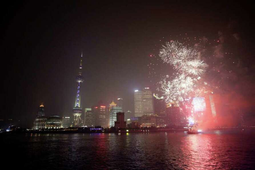 Oriental Pearl Tower, left, is illuminated with blue color and fire works are set off during an even