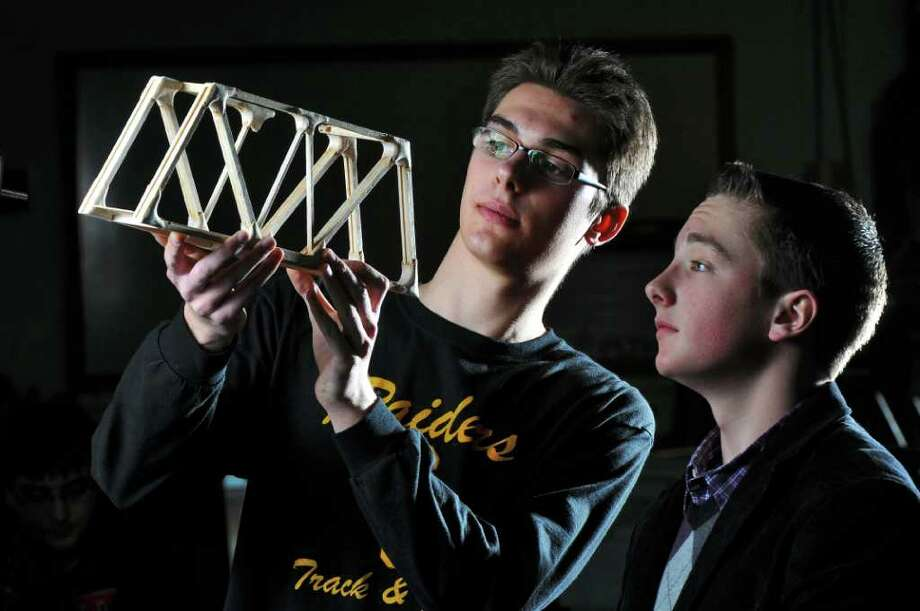Colonie High School juniors Collin Cragon, left, and Brighton Schwarz, right, look over Cragon's winning entry in the recent Model Bridge Contest, which he had built in the school's Principles of Engineering class, shown here on Monday March 5, 2012 in Colonie, N.Y. Cragon and Schwarz won first and second place, respectively, in the efficiency and load rating categories for their entries in the annual Capital District Engineers Week event, held last month. Colonie High students have won first place in the event for 14 years in a row. (Philip Kamrass / Times Union ) Photo: Philip Kamrass / 00016637A