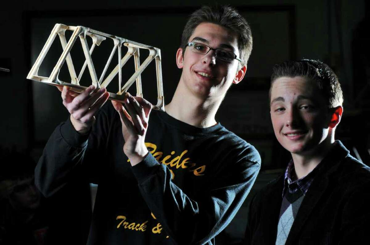 Colonie High School juniors Collin Cragon, left, and Brighton Schwarz, right, look over Cragon's winning entry in the recent Model Bridge Contest, which he had built in the school's Principles of Engineering class, shown here on Monday March 5, 2012 in Colonie, N.Y. Cragon and Schwarz won first and second place, respectively, in the efficiency and load rating categories for their entries in the annual Capital District Engineers Week event, held last month. Colonie High students have won first place in the event for 14 years in a row. (Philip Kamrass / Times Union )