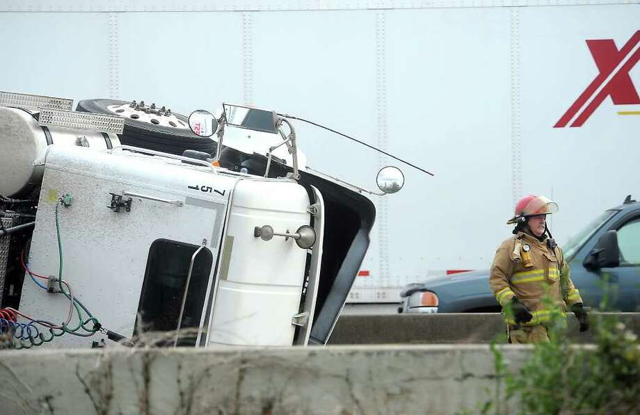Emergency officials respond to an overturned tractor trailer near the Downtown Exit on I10 in Beaumont, Tuesday, March 6, 2012. Tammy McKinley/The Enterprise Photo: TAMMY MCKINLEY