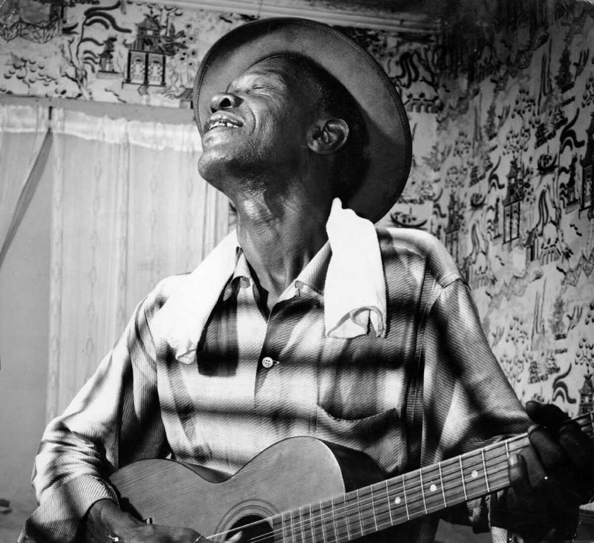 Blues guitarist Sam 'Lightnin' Hopkins photo from 1959. HOUCHRON CAPTION (03/31/2002): Hopkins' musical career started at age 8, when he made a guitar by cutting a hole in a cigar box, nailing on a plank of wood and stringing it with wire. This photo was taken in 1959.