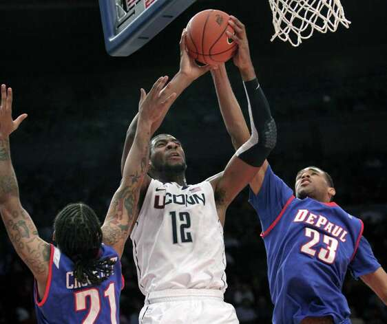 Connecticut's Andre Drummond, center, goes up for a shot past DePaul's Jamee Crockett, left, and Donnavan Kirk during the first round of the Big East NCAA college basketball conference tournament in New York, Tuesday, March 6, 2012.  (AP Photo/Seth Wenig) Photo: Seth Wenig, ASSOCIATED PRESS / AP2012