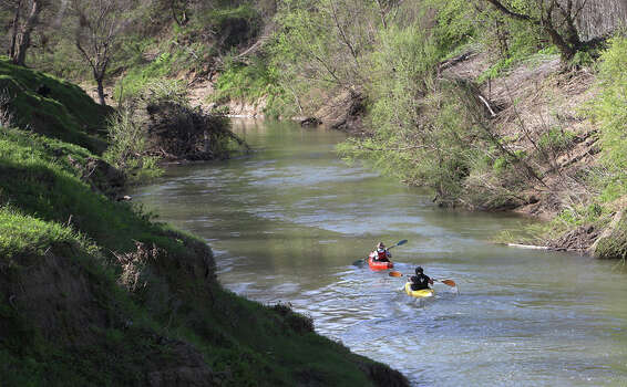 The banks along the San Antonio River along the new 12-mile Saspamco Paddling Trail in South Bexar County near Elmendorf are fairly high and surrounded by private land. However, there is a midway take out near County Road 125. Kayakers Kenny Munn (front) and stepson Michael Walker were one of the first to trek down the paddling trail on  Mar. 3, 2012. Photo: Kin Man Hui, Kin Man Hui/Express-News / © 2012 San Antonio Express-News
