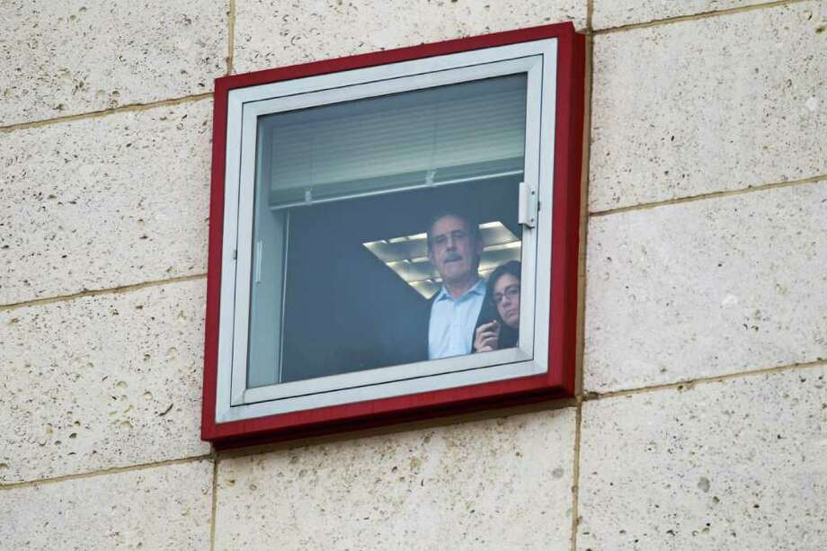R. Allen Stanford, left, looks out one of the windows of the Bob Casey Federal Courthouse with an unidentified woman, Tuesday, March 6, 2012, in Houston. Stanford was convicted embezzling $7 billion from his investors through a Ponzi scheme he operated for 20 years. Photo: Nick De La Torre, Houston Chronicle / © 2012  Houston Chronicle