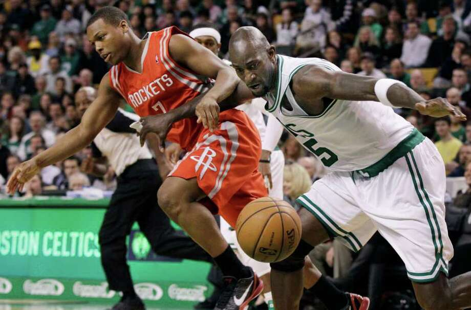 Boston Celtics forward Kevin Garnett (5) tracks down a loose ball against Houston Rockets guard Kyle Lowry (7) during the first half of an NBA basketball game in Boston Tuesday, March 6, 2012. (AP Photo/Elise Amendola) Photo: Elise Amendola, Associated Press / AP