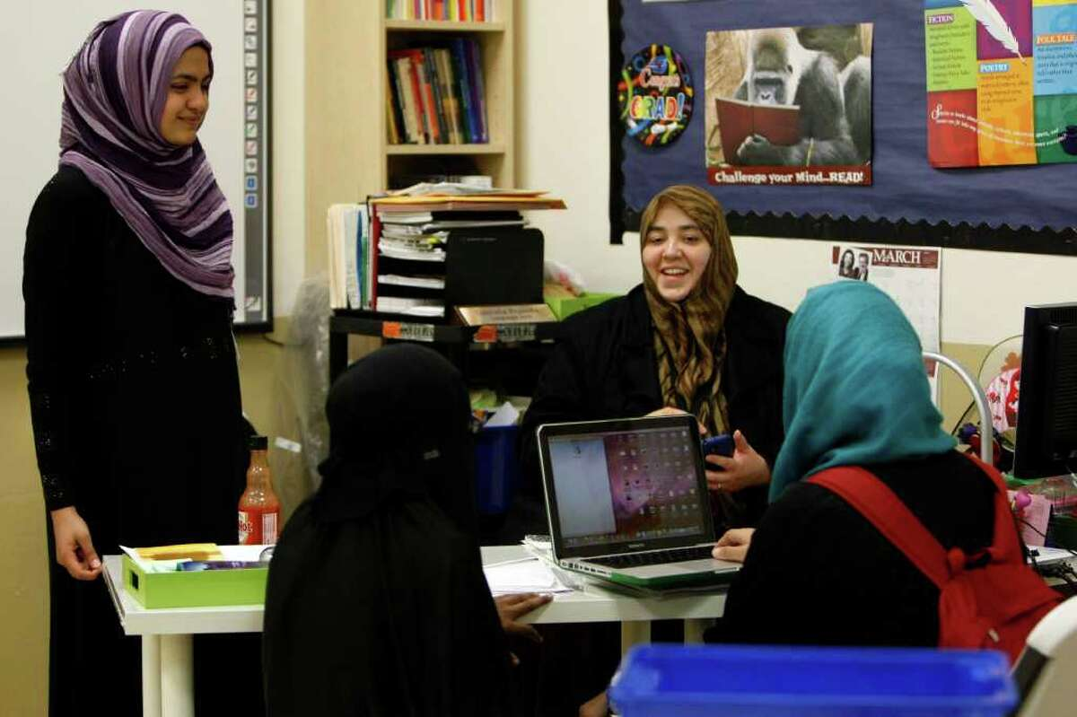 From left, Mahnoor Javed, Zaynab Abidogun and Maheen Gardezi listen to AP English teacher Gabriela Pruneda, center, at Iman Academy. The Texas Association of Private and Parochial schools rejected the school in 2010.