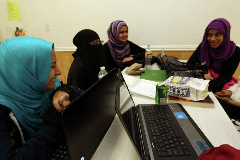 Seniors, at left, Maheen Gardezi, 17, Zaynab Abidogun, 16, Mahnoor Javed,17, and Aliya Bafagih, 17, right, talk about yearbook awards during lunch at Iman Academy. Photo: Johnny Hanson, Houston Chronicle / © 2012  Houston Chronicle
