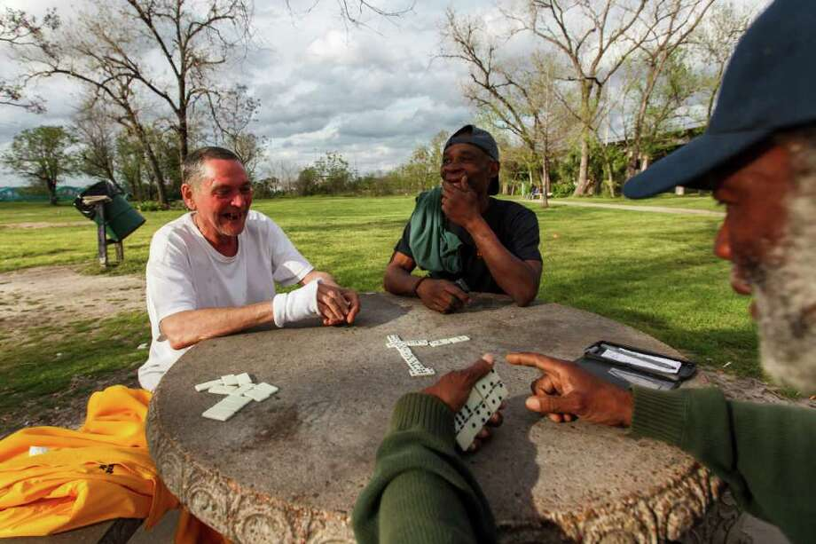 "Michael Gothann, left, Donald Johnson and Herman Bee, right, take advantage of  Tuesday's sunshine to play some dominoes at Bute Park. ""The people sitting at City Hall don't know what it's like out here,"" said Bee. Photo: Michael Paulsen / © 2012 Houston Chronicle"