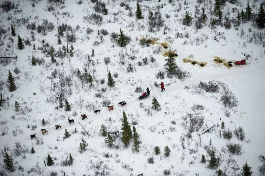 Two mushers talk on the trail across the Farewell Burn during the Iditarod Trail Sled Dog Race on Tuesday, March 6, 2012. Photo: Marc Lester, McClatchy-Tribune News Service / Anchorage Daily News