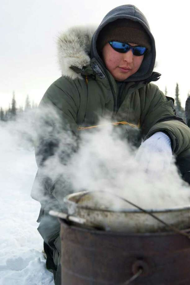 Mike Williams, Jr., cooks dog foot at the Nikolai checkpoint in Alaska during the Iditarod Trail Sled Dog Race on Tuesday, March 6, 2012. Photo: Marc Lester, McClatchy-Tribune News Service / Anchorage Daily News