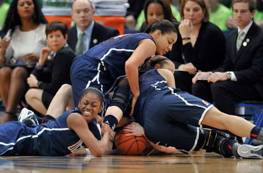 Connecticut's Tiffany Hayes, left, Bria Hartley, top, and Caroline Doty right, bury Notre Dame's Natalie Novosel, bottom, while chasing down a loose ball in the second half of an NCAA college basketball game in the final of the Big East women's tournament in Hartford, Conn., Tuesday, March 6, 2012.  Connecticut won 63-54. (AP Photo/Jessica Hill) Photo: Jessica Hill, Associated Press / AP2012