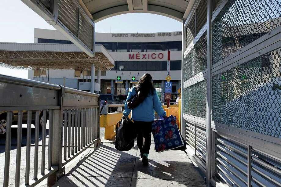 A pedestrians crosses an international bridge into Nuevo Laredo, Mexico. Some people feel such trips are dangerous. Photo: Express-News File Photo / glara@express-news.net