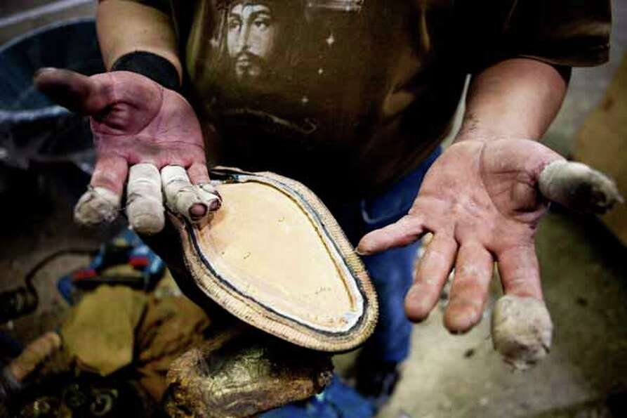 Jesus Adame shows his hands as he works on the bottom of a boot. Lucchese CEO Paul LaVoie explains t