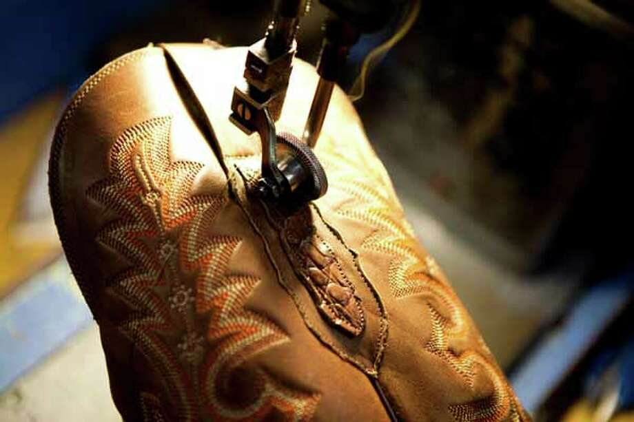 Antonio Garcia installs the pull tabs on a pair of boots with a sewing machine at the Lucchese Boot Company  factory in El Paso. Photo: Nick De La Torre, Houston Chronicle / Houston Chronicle
