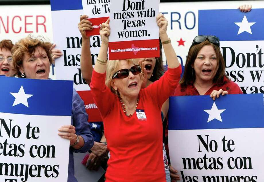 Mary Green, Peg Armstrong and Jan Perrault hold up signs during Women's Health Express, a bus event held to protest the attempt to cut Planned Parenthood out of Women's Health Plan in San Antonio, Texas on Tuesday, March 6, 2012. Photo: Helen L. Montoya, San Antonio Express-News / ©SAN ANTONIO EXPRESS-NEWS