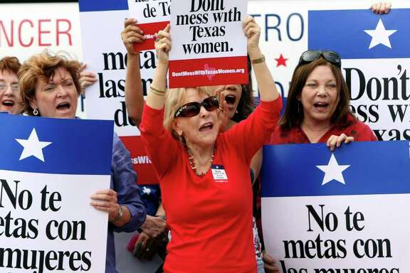 Mary Green, Peg Armstrong and Jan Perrault hold up signs during Women's Health Express, a bus event held to protest the attempt to cut Planned Parenthood out of Women's Health Plan in San Antonio, Texas on Tuesday, March 6, 2012.