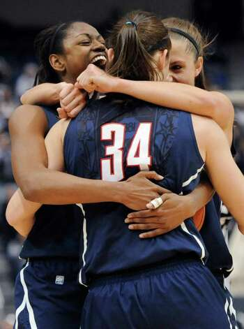 Connecticut's Tiffany Hayes, left, Kelly Faris (34) and Caroline Doty celebrate in the final minute of an NCAA college basketball game against Notre Dame in the final of the Big East women's tournament in Hartford, Conn., Tuesday, March 6, 2012. Connecticut won 63-54. (AP Photo/Jessica Hill) Photo: Jessica Hill
