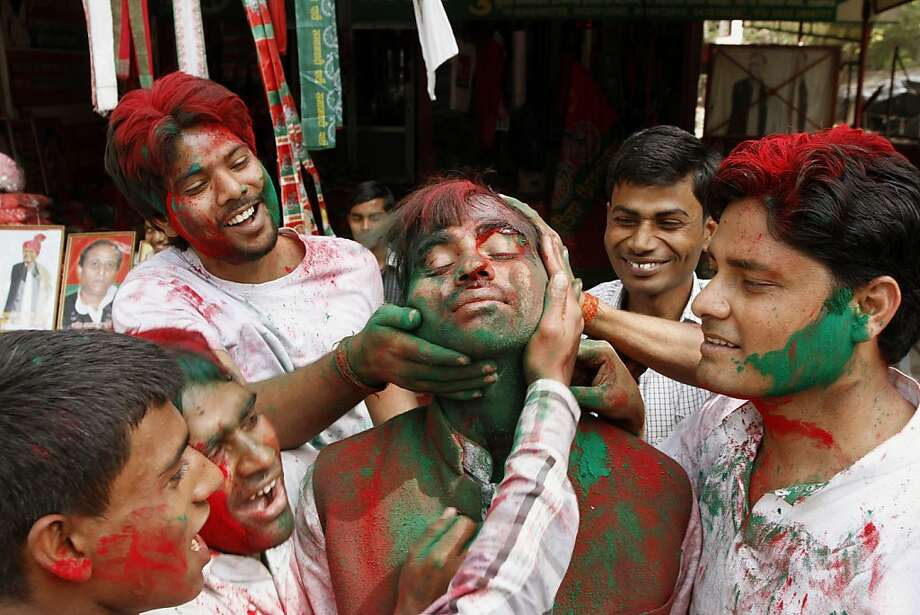 Samajwadi Party supporters smear party flag colored powder on each others' faces as they celebrate the early leads of the party leader Mulayam Singh Yadav outside the party office in Lucknow, India, Tuesday, March 6, 2012. Election officials across five Indian states Tuesday began counting votes in crucial provincial elections that are being seen as a test of strength for the country's ruling Congress party. (AP Photo/Rakesh Kumar Singh) Photo: Rajesh Kumar Singh, Associated Press