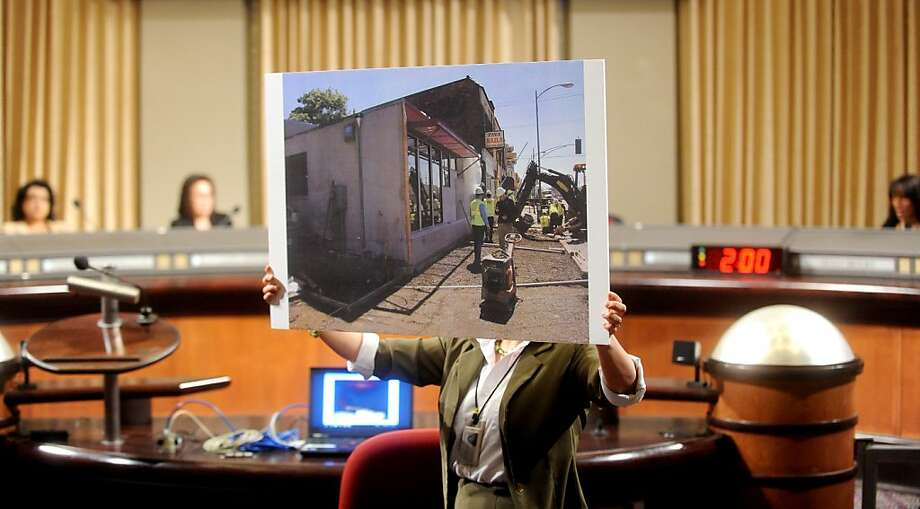 Clara Garzon, aide to Oakland City Councilwoman Desley Brooks, displays a picture of the Digital Arts and Culinary Academy during a council meeting on Tuesday, March 6, 2012, in Oakland, Calif. Photo: Noah Berger, Special To The Chronicle