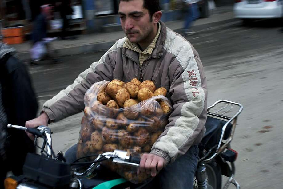 "A man rides his motorcycle after buying potatoes in a street market in Idlib, north Syria, Tuesday, March 6, 2012. Syria's president defied mounting international pressure to end the year-old crackdown on an uprising against him and said Tuesday he was determined to go on fighting what he called ""foreign-backed terrorism."" The U.N. says more than 7,500 people have been killed since Syria's uprising started in March 2011.  (AP Photo/Rodrigo Abd) Photo: Rodrigo Abd, Associated Press"