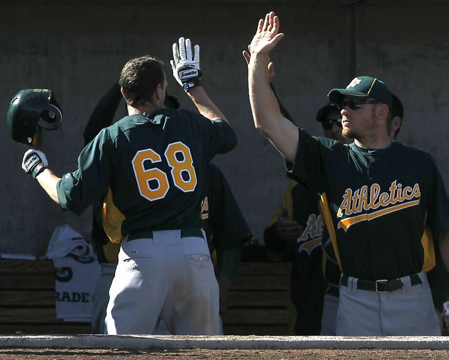 Jeff Fiorentino (68) is welcomed back to the dugout after scoring a run in the 9th inning of the Oakland A's Cactus League spring training game against the Milwaukee Brewers in Phoenix, Ariz. on Tuesday, March 6, 2012. Photo: Paul Chinn, The Chronicle