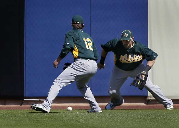 Collin Cowgill (12) and Jonny Gomes had trouble handling a double by Jonathan Lucroy, one of only two hits allowed by Oakland pitchers, in the A's Cactus League spring training game against the Milwaukee Brewers in Phoenix, Ariz. on Tuesday, March 6, 2012. Photo: Paul Chinn, The Chronicle