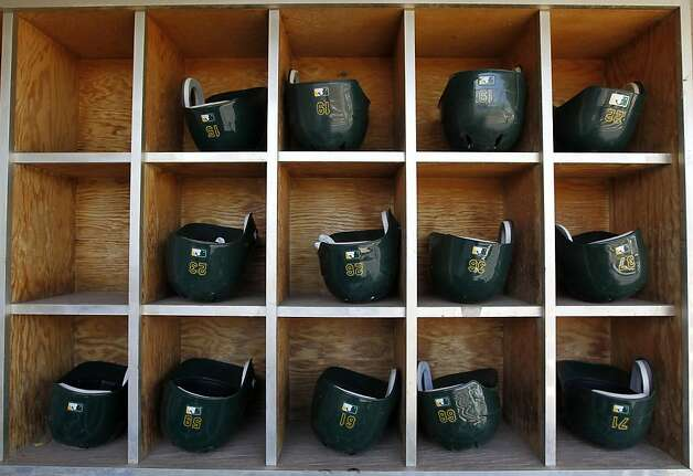 Batting helmets are arranged in the dugout before the Oakland A's Cactus League spring training game against the Milwaukee Brewers in Phoenix, Ariz. on Tuesday, March 6, 2012. Photo: Paul Chinn, The Chronicle
