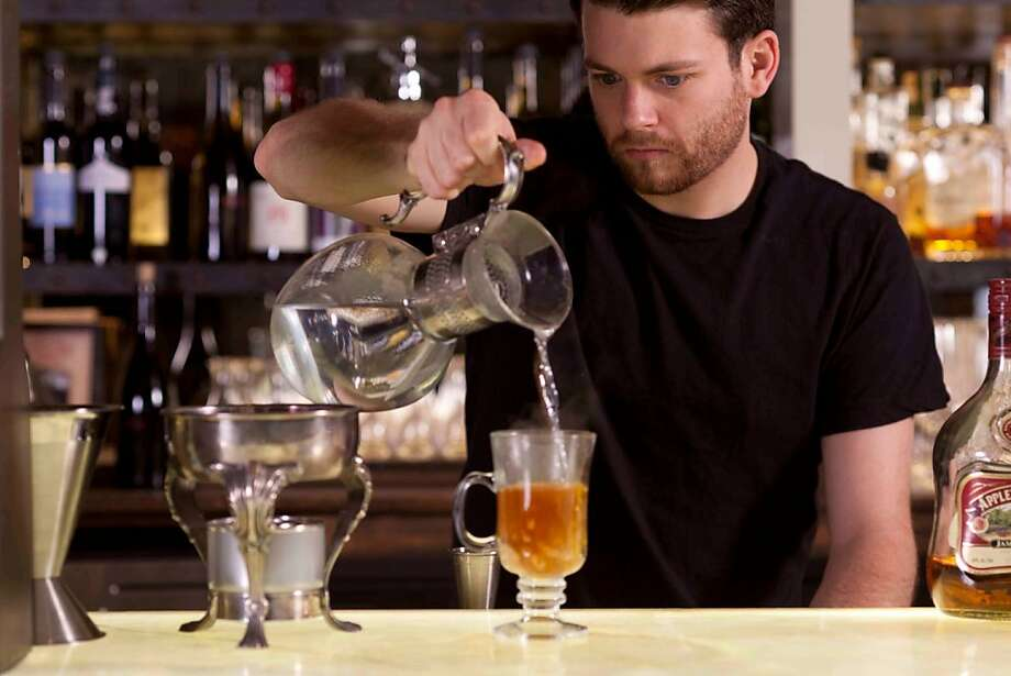 A bartender prepares one of Restaurant 1833's signature cocktails. The list of $10 mixed drinks includes whimsical choices like the Kentucky Waffle with 10-year bourbon, lemon, maple syrup, apple cider and cinnamon stick. Photo: Restaurant 1833