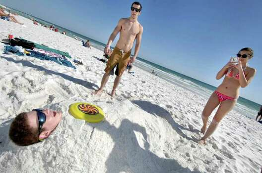 Tara Demkowicz, right, takes a picture of fellow spring breaker Robert Barkley, left, after she and David Stevens, center, buried Barkley in the sand on Okaloosa Island beach in Fort Walton Beach, Fla. on Monday,  March 5, 2012. (AP Photo/Northwest Florida Daily, Devon Ravine) Photo: Devon Ravine, Associated Press / Northwest Florida Daily News