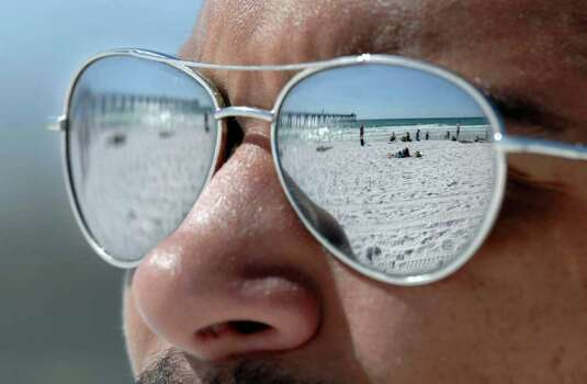 Blue sky, white sand and spring breakers are reflected in the sunglasses of University of Florida student Luc Lawrence as he and friends enjoy a warm sunny day on Okaloosa Island beach in Fort Walton Beach, Fla. on Monday,  March 5, 2012. (AP Photo/Northwest Florida Daily, Devon Ravine) Photo: Devon Ravine, Associated Press / Northwest Florida Daily News