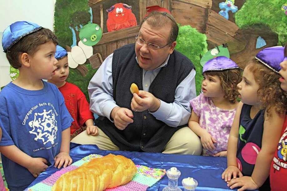 Congregation Beth El Rabbi Seth Stander shares bread with the preschoolers from the toddlers class of teachers Tracy Weiss and Yukari Bromfield at the temple  at 3900 Raoul Wallenberg Lane in Missouri City. The congregation is marking its 30th anniversary. Photo: Suzanne Rehak