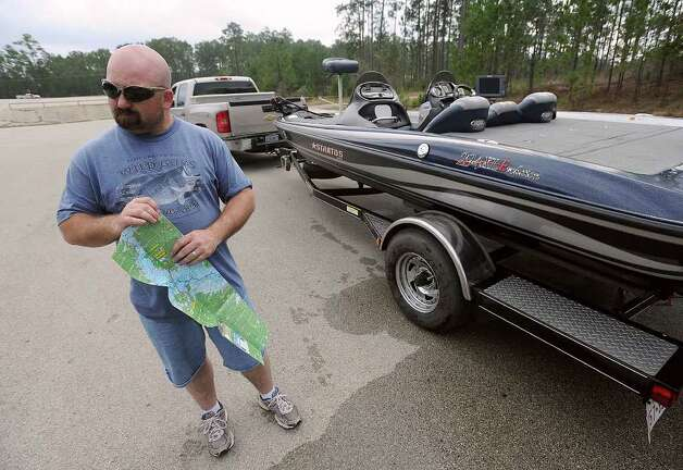 Cody Kane folds a map after fishing on Sam Rayburn Reservoir on Thursday. Kane said he was pleased to see many areas on the water reopened from last year's drought. Photo taken Thursday March 2, 2012 Guiseppe Barranco/The Enterprise Photo: Guiseppe Barranco, STAFF PHOTOGRAPHER / The Beaumont Enterprise