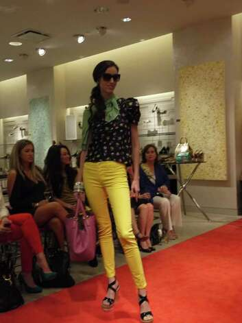 A Neiman Marcus model wears bright yellow skinny jeans with a printed top. Photo: Michael Quintanilla/San Antonio Express-News / Michael Quintanilla