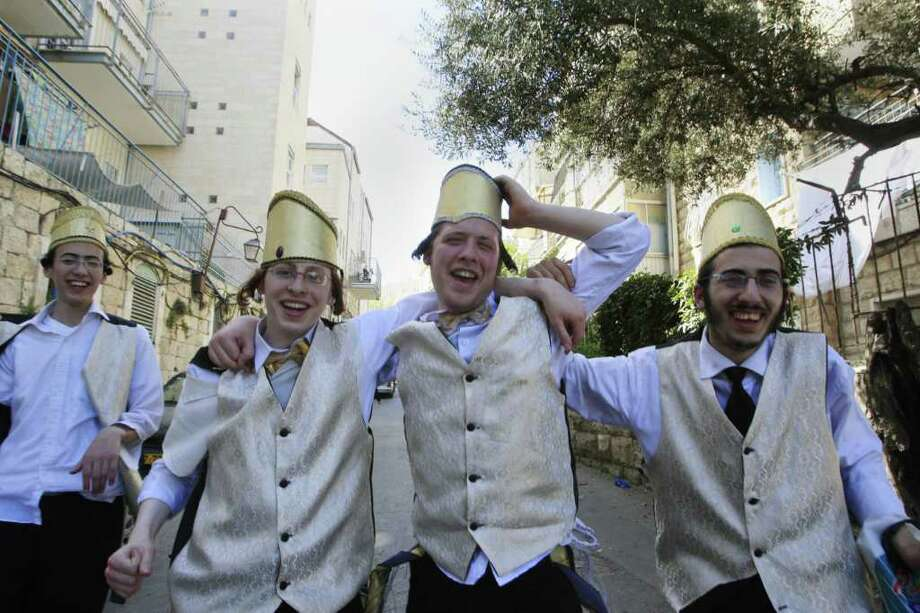 Ultra Orthodox Israeli Jews dressed for the festival of Purim walk in the streets of Jerusalem on March 23, 2008. The Jewish feast of Purim commemorates the salvation of the Jews from the ancient Persians as described in the book of Esther and celebrations often involve much drinking of alcohol. AFP PHOTO/MEHDI FEDOUACH Photo: MEHDI FEDOUACH, AFP/Getty Images / AFP