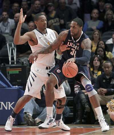 Connecticut's Alex Oriakhi, right, drives against West Virginia's Dominique Rutledge during the second round of the Big East NCAA college basketball conference tournament in New York, Wednesday, March 7, 2012. (AP Photo/Seth Wenig)