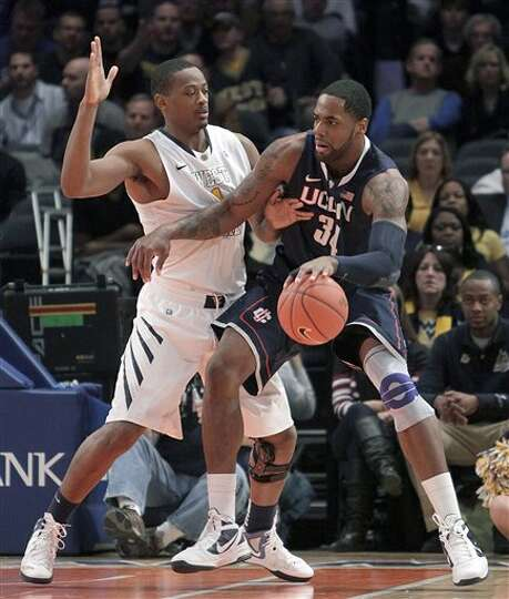 Connecticut's Alex Oriakhi, right, drives against West Virginia's Dominique Rutledge during the seco