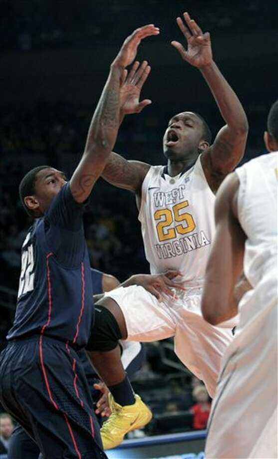 West Virginia's Darryl Bryant is fouled by Connecticut's Roscoe Smith, left, during the second round of the Big East NCAA college basketball conference tournament in New York, Wednesday, March 7, 2012. (AP Photo/Seth Wenig)