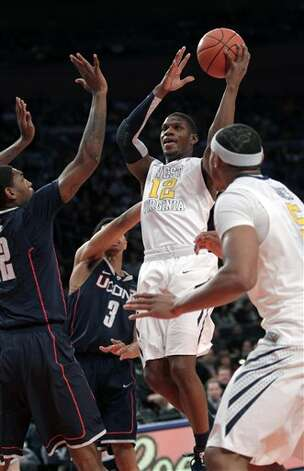 West Virginia's Aaron Brown, center, looks to pass through Connecticut defenders during the second round of the Big East NCAA college basketball conference tournament in New York, Wednesday, March 7, 2012. (AP Photo/Seth Wenig)